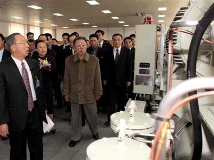 Kim Jong Il looking at machines in a DPRK production facility