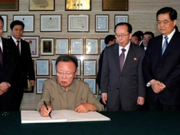 Kim Jong Il signing a document while Hu Jintao watches him