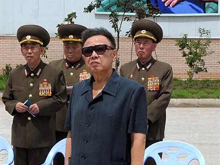 Kim Jong Il surrounded by generals visiting a tile factory in 2009
