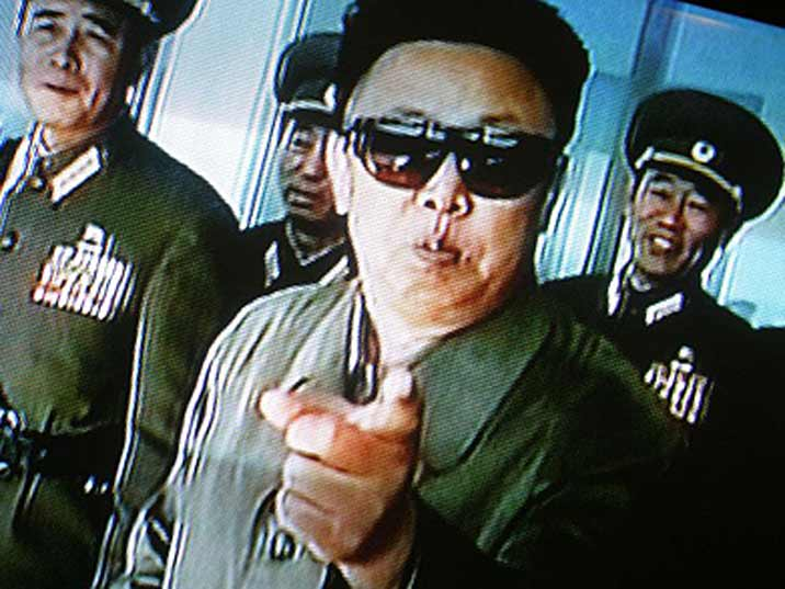 Kim Jong Il pointing at the camera while walking with his generals