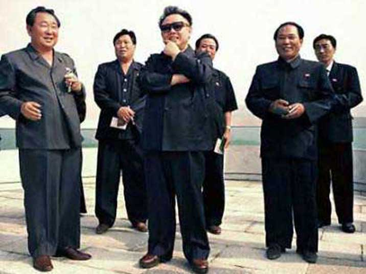 Kim Jong Il looking at something surrounded by his followers