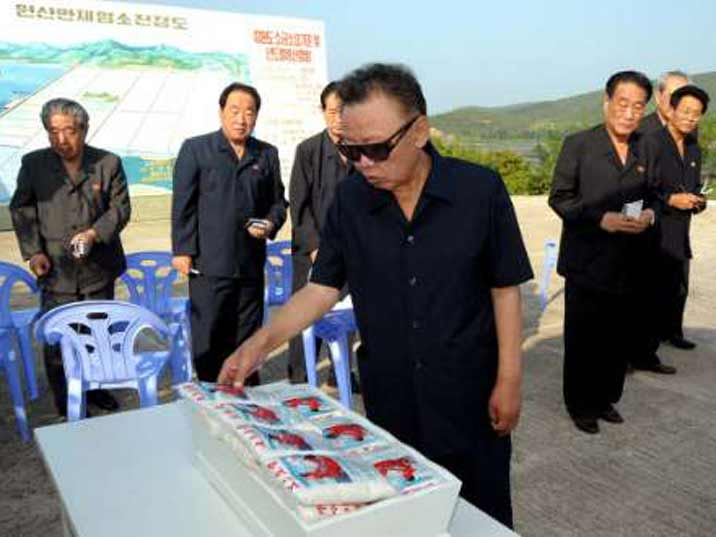 Kim Jong Il looking at rice produced on a state farm were he just gave valuable field guidance