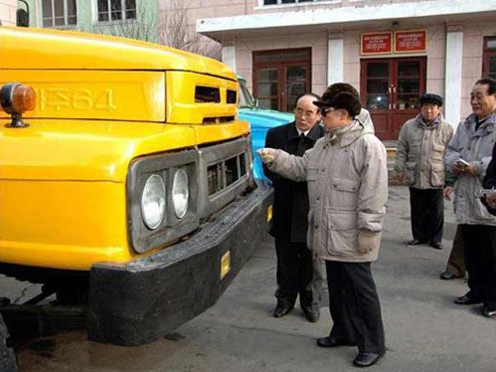 Kim Jong Il looking at a yellow Chinese made truck