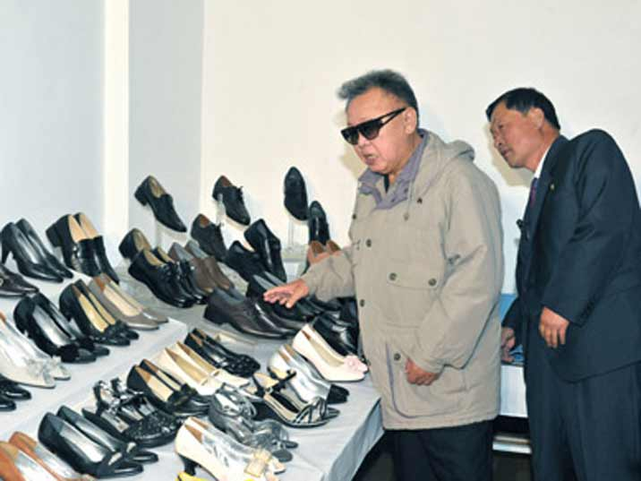Kim Jong Il looking at ladies shoes in the Phyongsong Synthetic Leather Factory