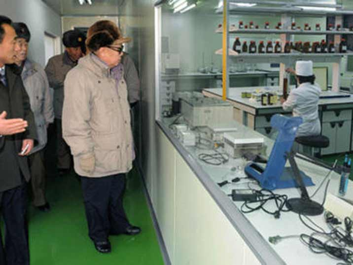 Kim Jong Il looking at a female worker in a laboratory