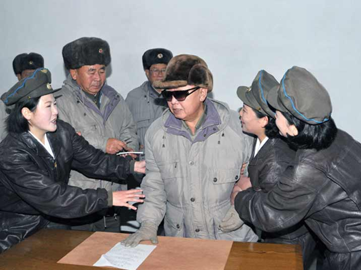 Kim Jong Il looking at a piece of paper with female soldiers while visiting an army base