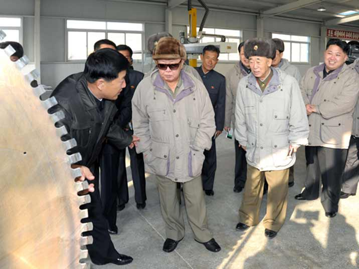 Kim Jong Il looking at an industrial saw with his son Kim Jung Un