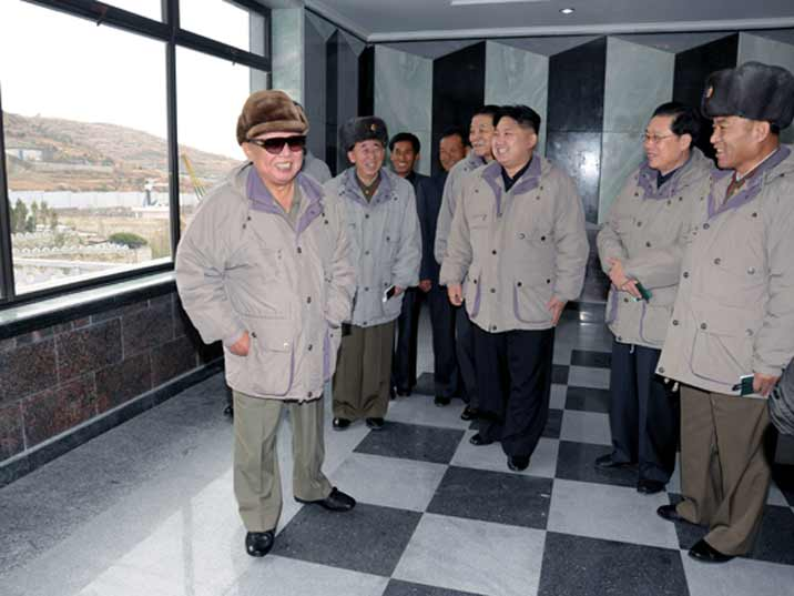 Kim Jong Il looking at a room in a North Korean harbour town