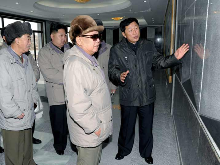 Kim Jong Il looking at tiles with his son Kim Jung Un