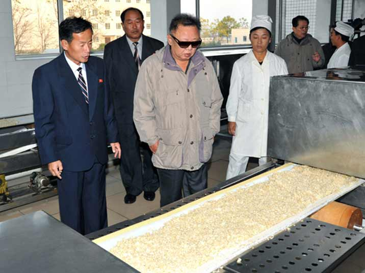 Kim Jong Il looking at dough in a cookie factory