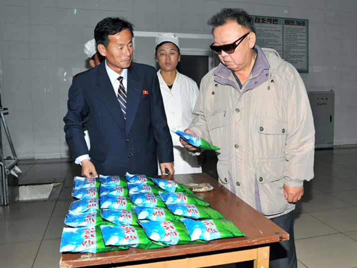 Kim Jong Il looking at crisps in the factory where they were produced