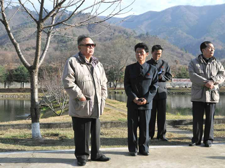 Kim Jong Il looking at then future near a pond in a beautiful landscape