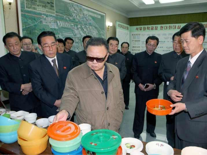 Kim Jong Il looking at kitchen appliances with many onlookers