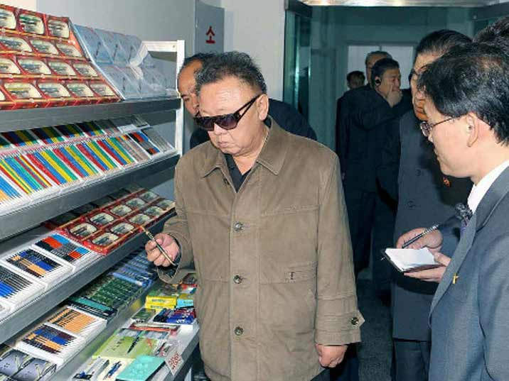 Kim Jong Il looking at a pencil in the Pencil factory