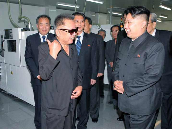 Kim Jong Il looking at Kim Jong Un in a production facility