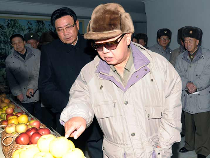 Kim Jong Il looking at apples while giving field guidance in Kwail County
