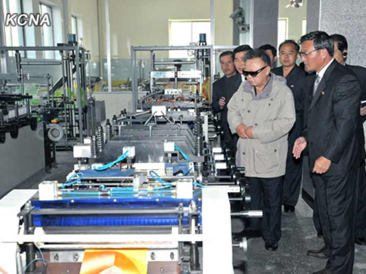 Kim Jong Il looking at machines at the Raknang Disabled Soldiers' Essential Plastic Goods Factory