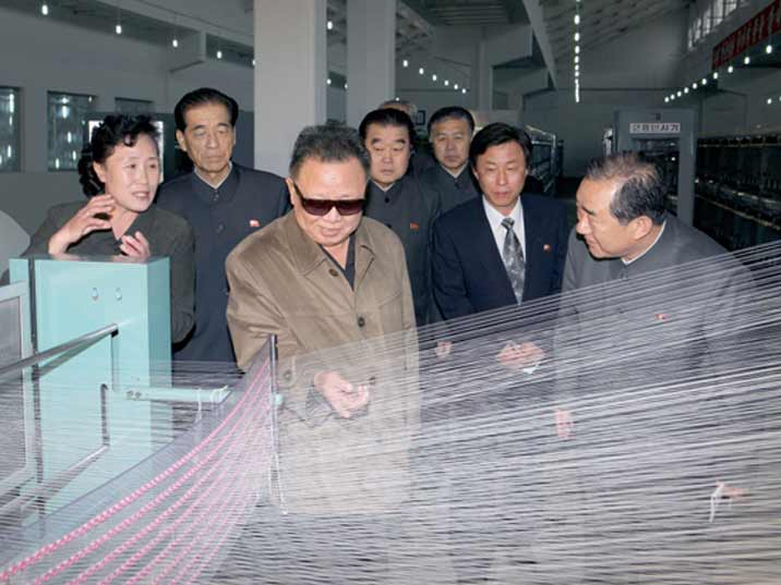 Kim Jong Il looking at a loom during field Guidance to various Light Industry Factories