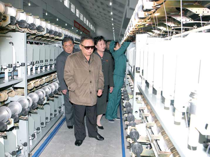 Kim Jong Il looking at treads during field Guidance to various Light Industry Factories