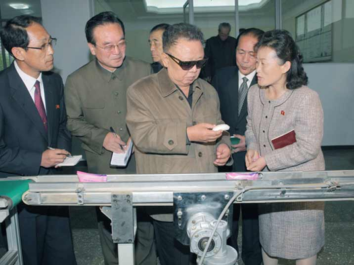 Kim Jong Il looking at womans hygiene products during field Guidance to various Light Industry Factories