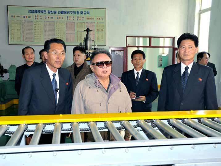 Kim Jong Il looking at a production belt during Field Guidance to Major Industrial Establishments in Hamhung