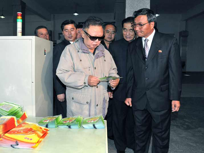 Kim Jong Il looking at leaflets during Field Guidance to Rangnang Disabled Soldiers Essential Plastic Goods Factory