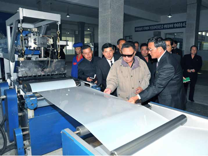 Kim Jong Il looking at plastic during Field Guidance to Rangnang Disabled Soldiers Essential Plastic Goods Factory