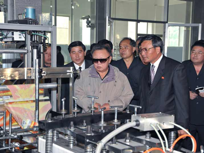 Kim Jong Il looking at packaging machine Field Guidance to Rangnang Disabled Soldiers Essential Plastic Goods Factory
