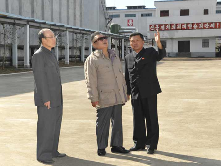 Kim Jong Il looking at factory