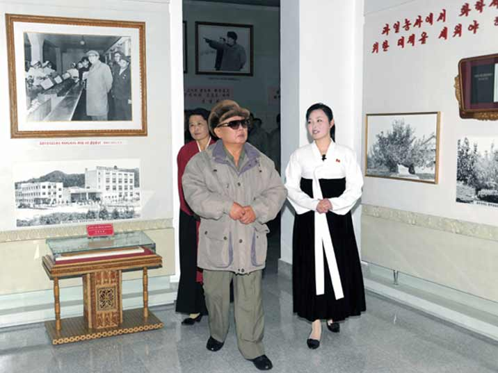 Kim Jong Il looking at a small museum dedicated to the history of the visited company