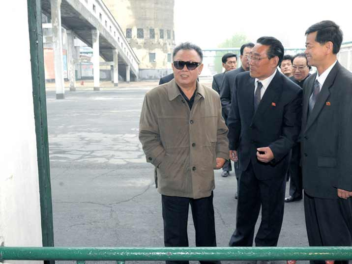 Kim Jong Il looking at the exterior of an industrial complex