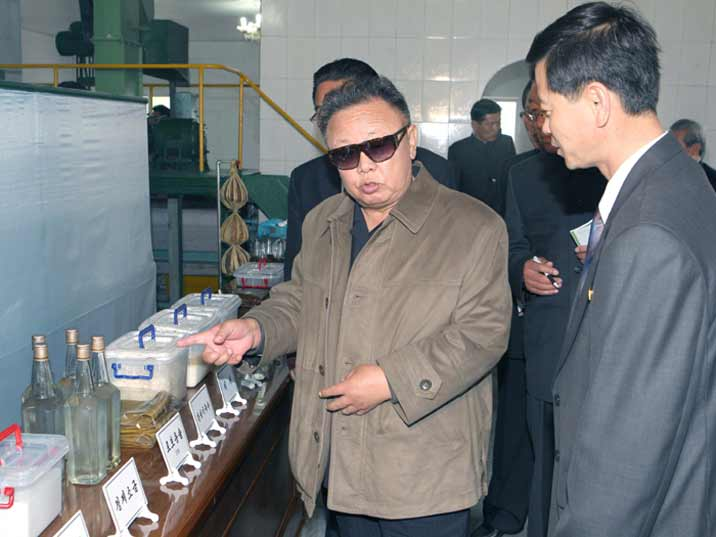 Kim Jong Il looking at various kitchen products like flower and vinegar