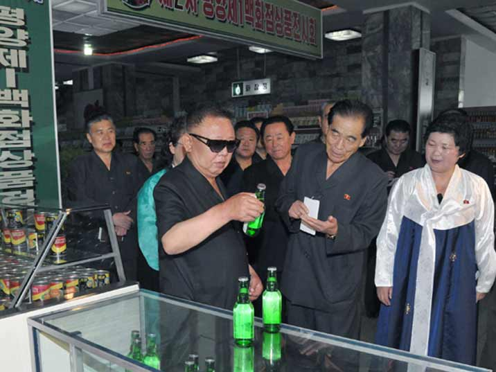 Kim Jong Il looking at water in a supermarket