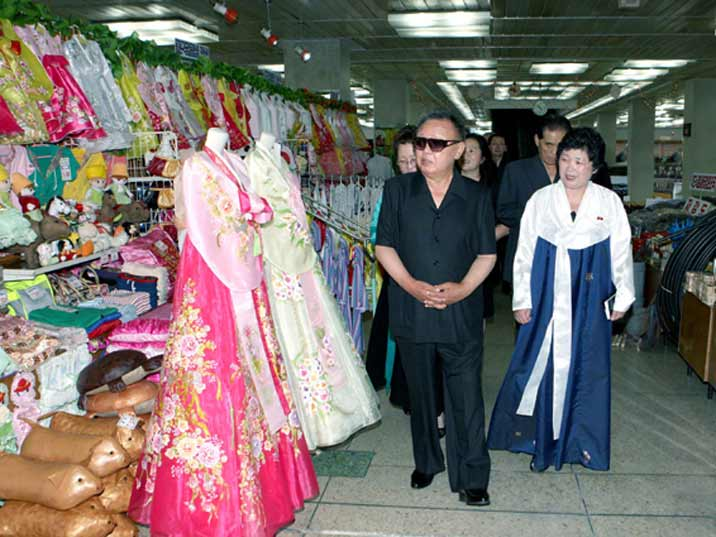 Kim Jong Il looking at traditional Korean dresses on display in a Pyongyang warehouse