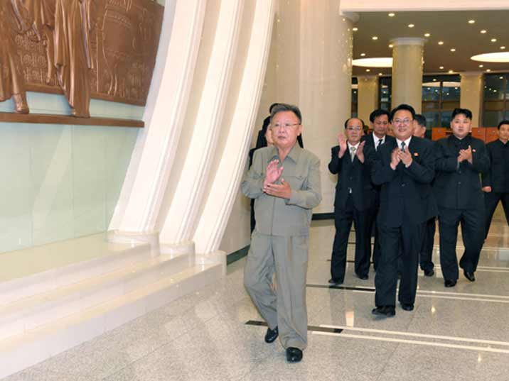 Kim Jong Il looking at applauding while entering a building with his heir Kim Jung Un