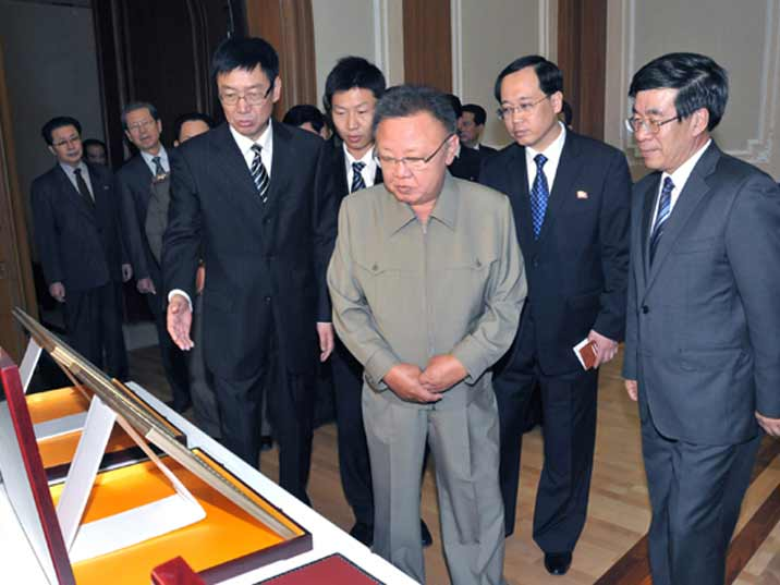 Kim Jong Il looking at a picture offered by a Chinese trade delegation