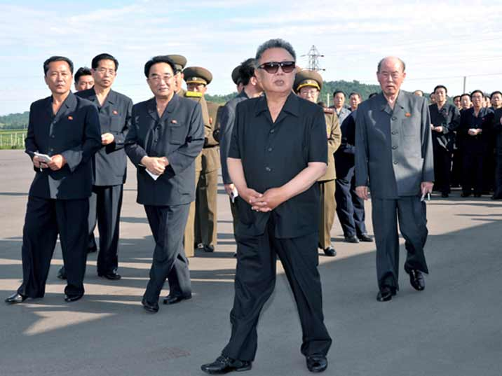 Kim Jong Il looking at something together with a large group of onlookers