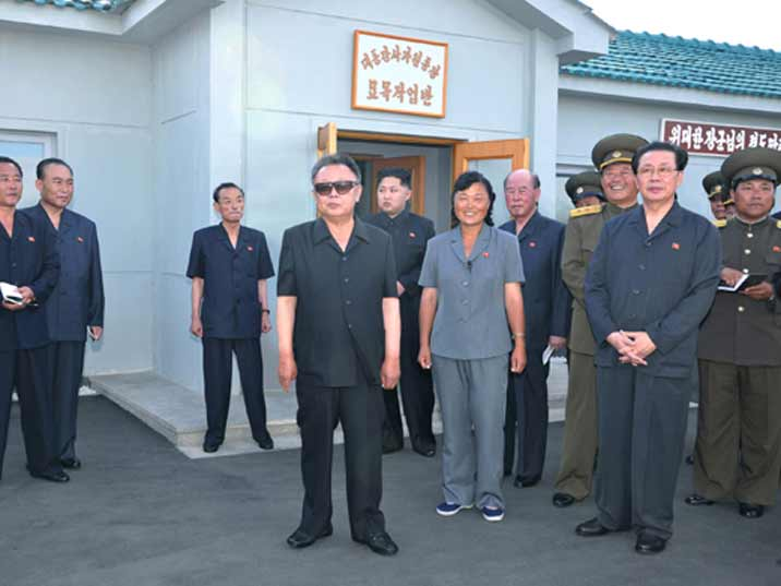 Kim Jong Il posing with a group of smiling people