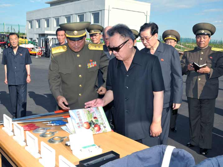 Kim Jong Il looking at leaflets about fruits on a farm run by the North Korean military