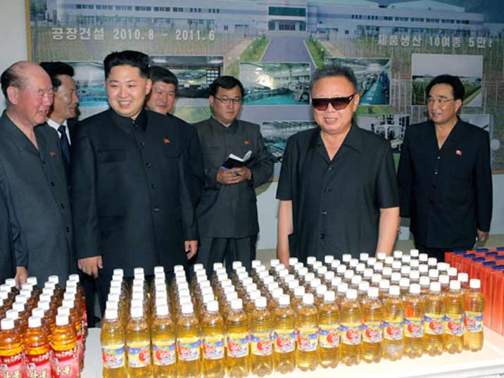 Kim Jong Il looking at fruit juice produced on a model farm