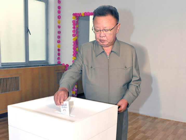 Kim Jong Il looking at his vote during elections