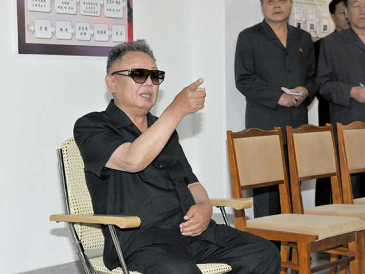 Kim Jong Il pointing at something while sitting down