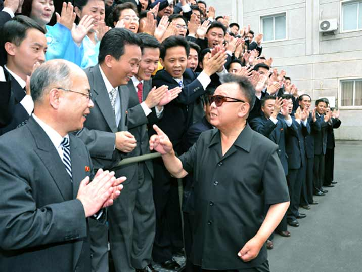 Kim Jong Il looking at a worker ready for a group photo together with Kin Jong Il