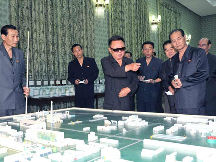 Kim Jong Il looking at a scale model of an industrial complex