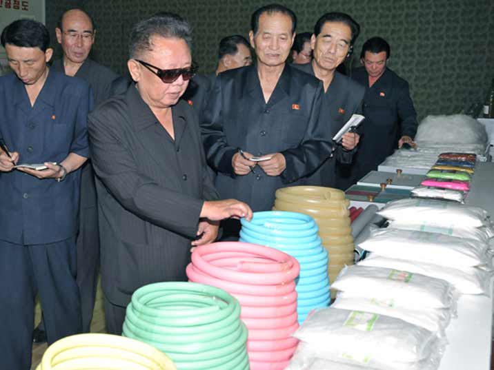 Kim Jong Il looking at hoses in various colours