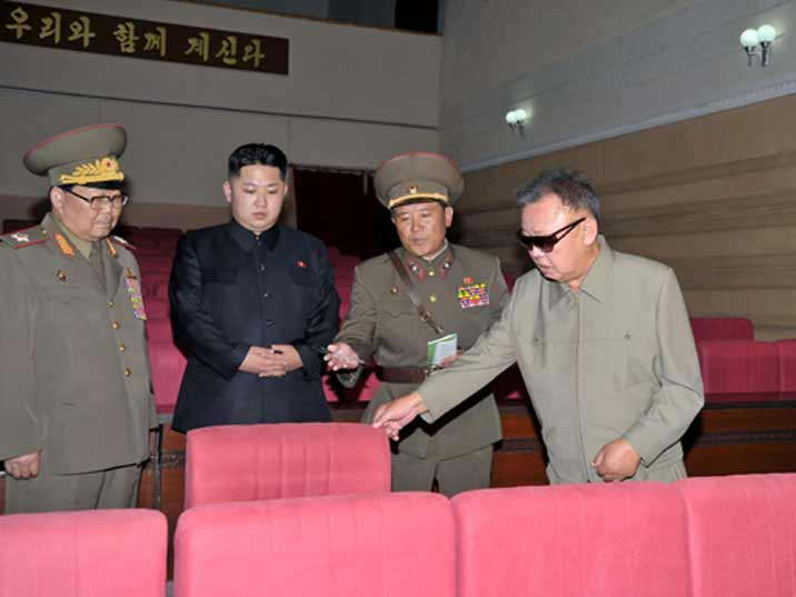 Kim Jong Il looking at a chair in a newly build theatre