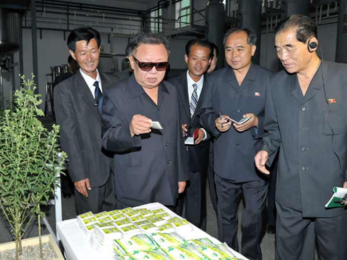 Kim Jong Il looking at fertilizer on a production facility