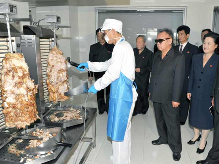Kim Jong Il looking at Kebab being cut of for a tasty sandwich