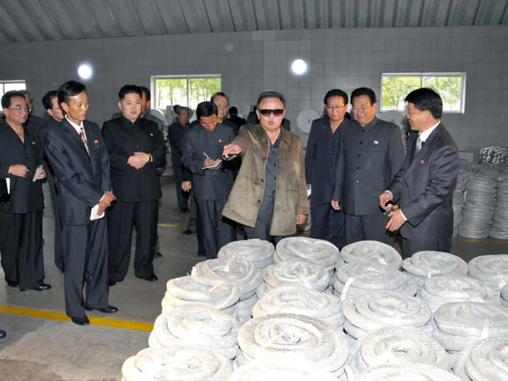 Kim Jong Il looking at cotton products
