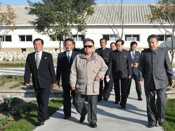Kim Jong Il looking at a farm with some of the managers
